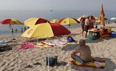 Plantan doce sombrillas con los colores de la bandera de España en la playa de Arenys de Mar
