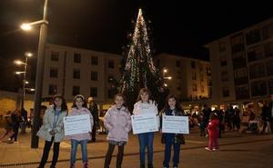 Las niñas ganadoras del concurso de postales de Medina de Pomar encienden las luces navideñas