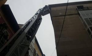 Los bomberos retiran dos piezas de piedra a punto de caer de la cornisa de la Cámara de Comercio